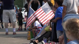 People waving American flags at July 4th parade 4k