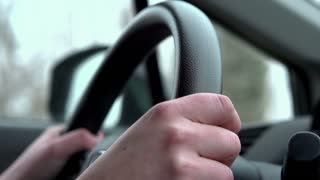 Person driving car steering wheel shot slow motion