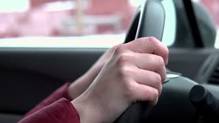 Person driving car with hand on wheel slow motion