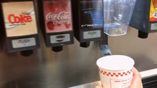 Person filling drink cup with diet coke at restaurant