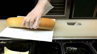 Person preparing a sub at restaurant 4k