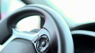 Person spinning steering wheel in slow motion