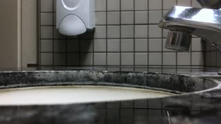 Person using foam soap to wash hands in restroom 4k