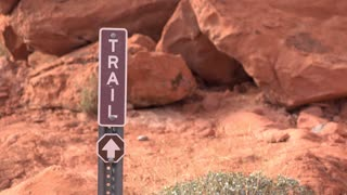 Person walking by trail direction sign in mountain area 4k