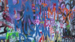 Person writing on Lennon Wall in Prague