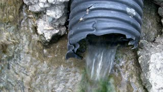 Plastic Hose Draining Water out of Rocks