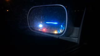Police lights flashing in side view mirror of car