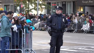 Police officer standing along fence of 89th annual Macy's Parade route 4k