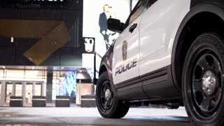 Police vehicle parked in front of mall entrance in snow 4k