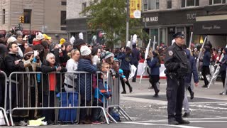 Police with crowd of people behind fence at Macys Parade 4k