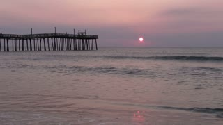 Quiet morning beach scene with Pier and sunrise