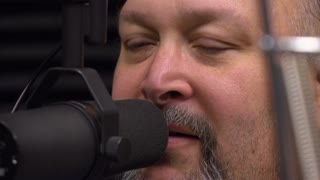 Radio personality talking into microphone at recording studio 4k