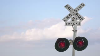 Railroad crossing sign with blue sky in background 4k