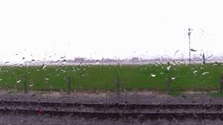 Rain drops on train window in motion