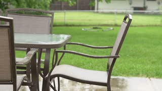 Rain falling on backyard patio furniture slow motion