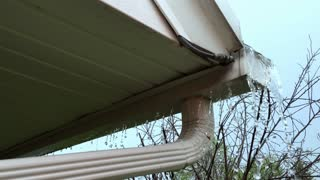 Rain storm flooding gutter on home