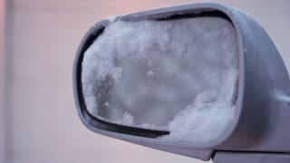 Rear view mirror of car covered in snow 4k