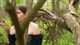 Renaissance girl in woods smiling and looking around