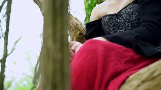 Renaissance girl sitting in woods tilt shot 4k