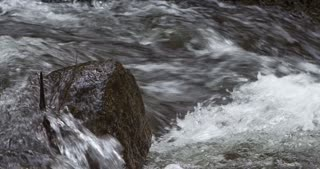 Rock with water rushing around it in stream 4k.