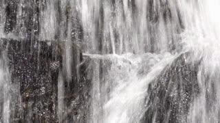 Rocks being splashed by waterfall water crashing down 4k