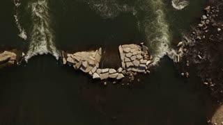 Rocks in stream creating natural dam aerial view