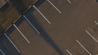 Rotating above empty parking spots in lot aerial view 4k