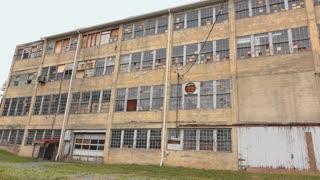 Rundown abandoned warehouse building establishing shot 4k