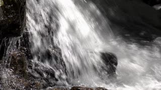 Rushing water smashing down onto rock floor 4k