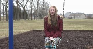 Sad and depressed girl sitting on swing 4k