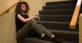 Sad and depressed young girl sitting in stairwell 4k