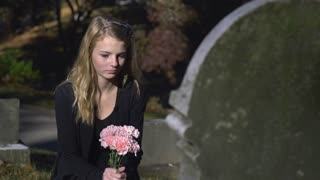 Sad girl sitting at gravestone in cemetery holding pink flowers 4k