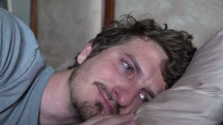 Sad man missing someone while laying in bed