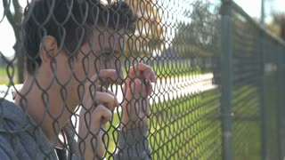 Sad man standing against fence thinking about something 4k