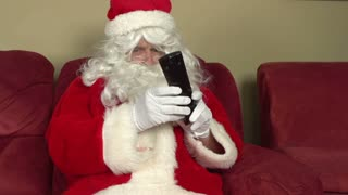 Santa watching television with remote in hand