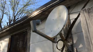 Satellite dish in backyard of old house