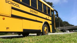 School bus sitting on side of street waiting.