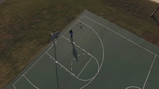 School yard basketball court with boy practicing aerial view 4k