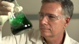 Scientist shaking green fluid in beaker