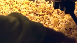 Scooping Popcorn from machine