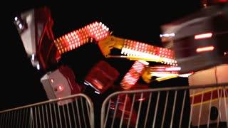 Scrambler Carnival ride at Night behind fence