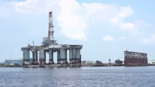 Seagull flying by oil rig in slow motion