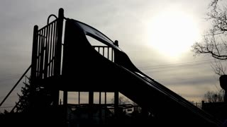 Shadow of kid waving on playground slide