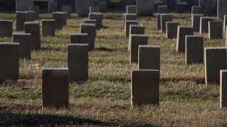 Shadow of person walking by graves in daylight 4k