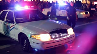 Sheriff walks around car at Endymion parade