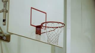 Shooting ball at indoor basketball hoop