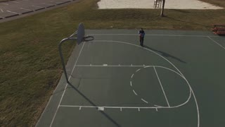 Shooting practice shots on basketball court aerial view 4k