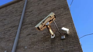 Side of building with large security camera 720p