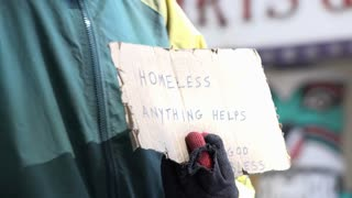 Sign held by homeless man asking for anything that could help 4k