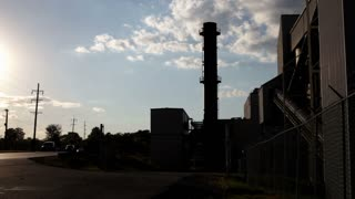 Silhouette of Factory next to road